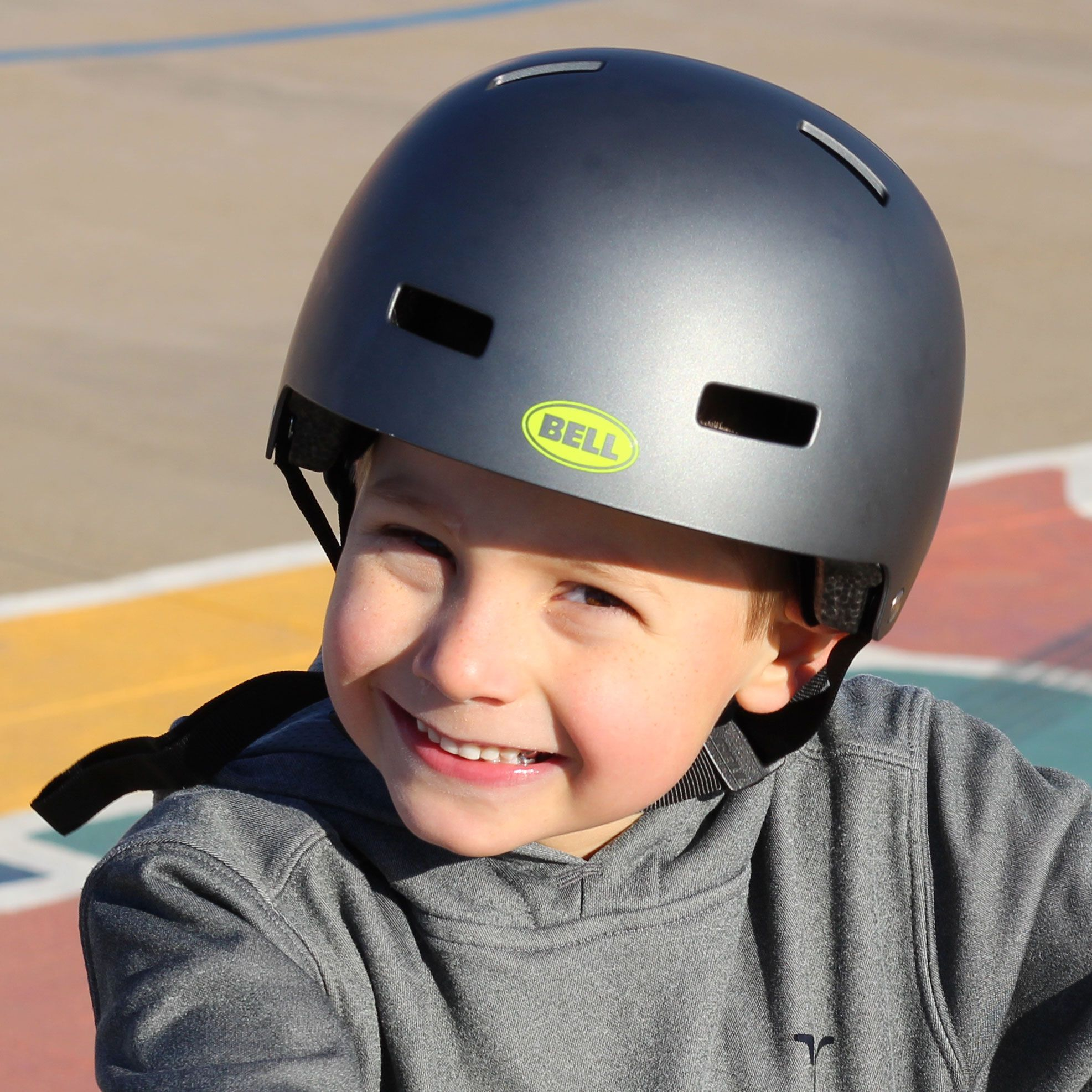 Boy smiling wearing a Bell block kid's skater-style helmet.