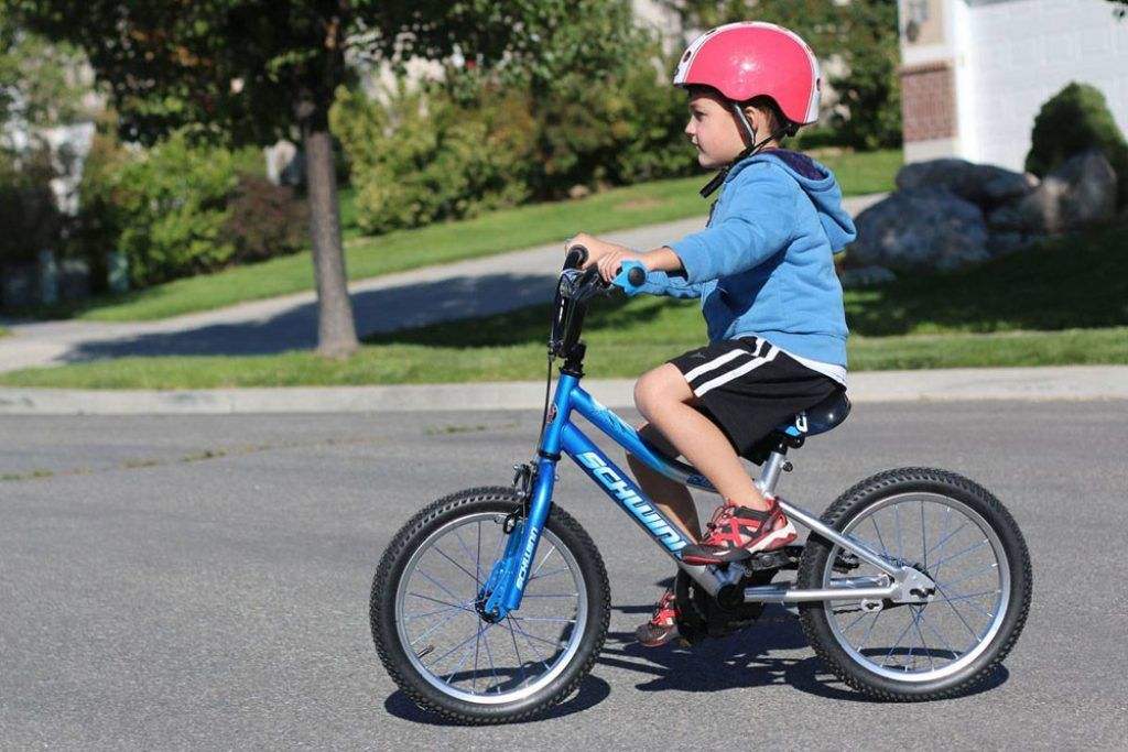 boy riding a blue schwinn smartstart 16 inch bike