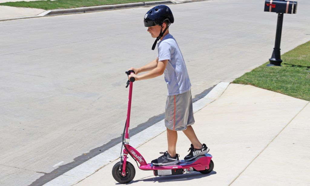 boy riding a pink E100 electric scooter
