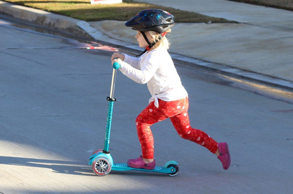 young girl riding a blue micro mini kick scooter