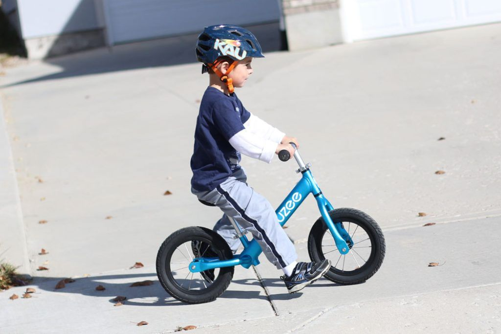 boy riding a blue cruzee balance bike