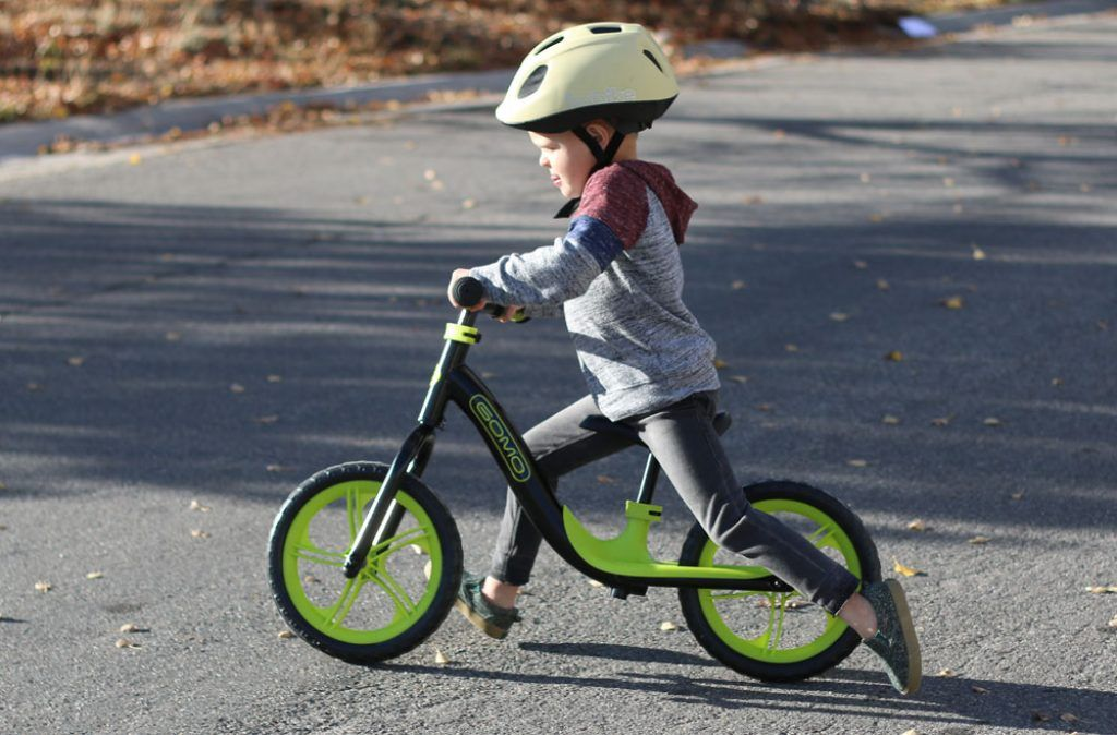 boy riding a green and black gomo balance bike