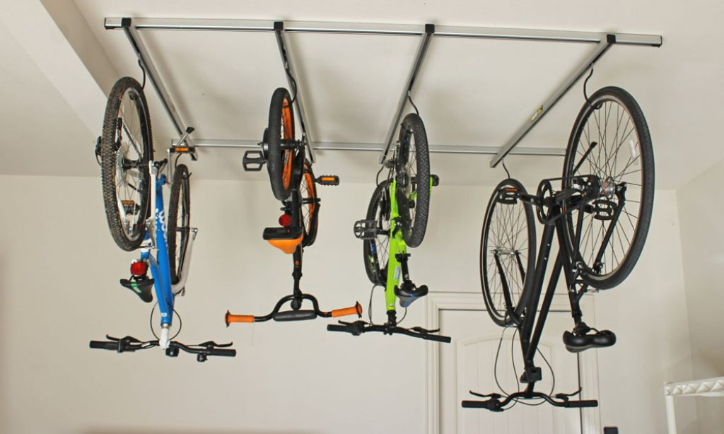 four bikes hanging on the ceiling from a saris cycle glide bike rack