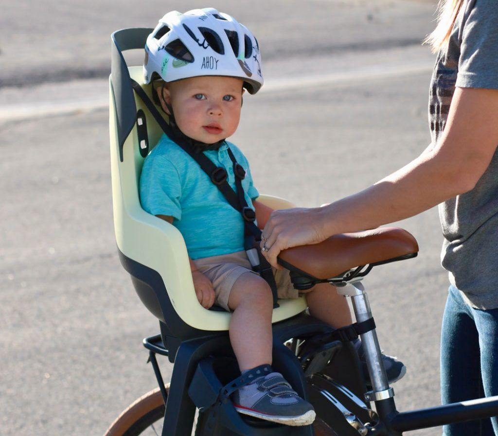 toddler getting buckled into the bobike Go child bike seat