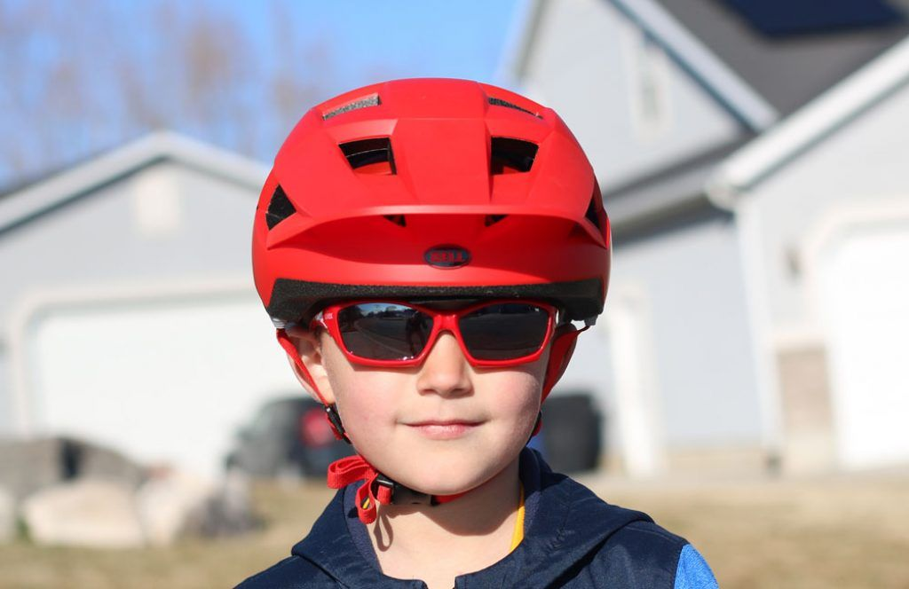 young boy facing the camera wearing a red bell spark jr biking helmet