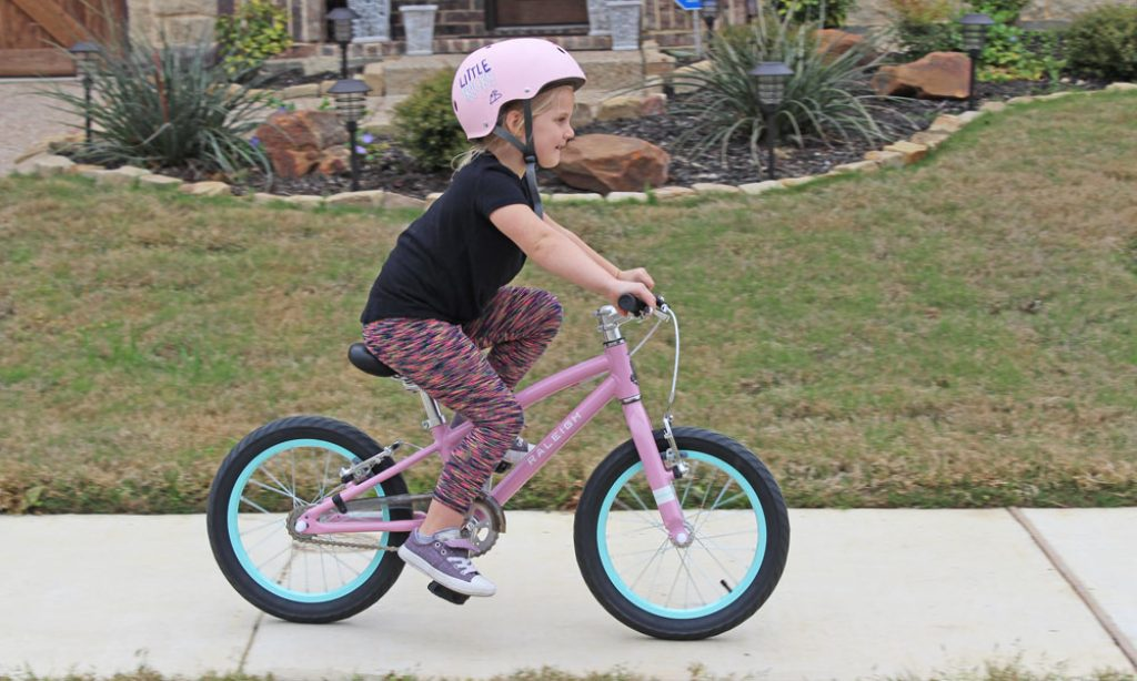young girl riding a raleigh lily 16