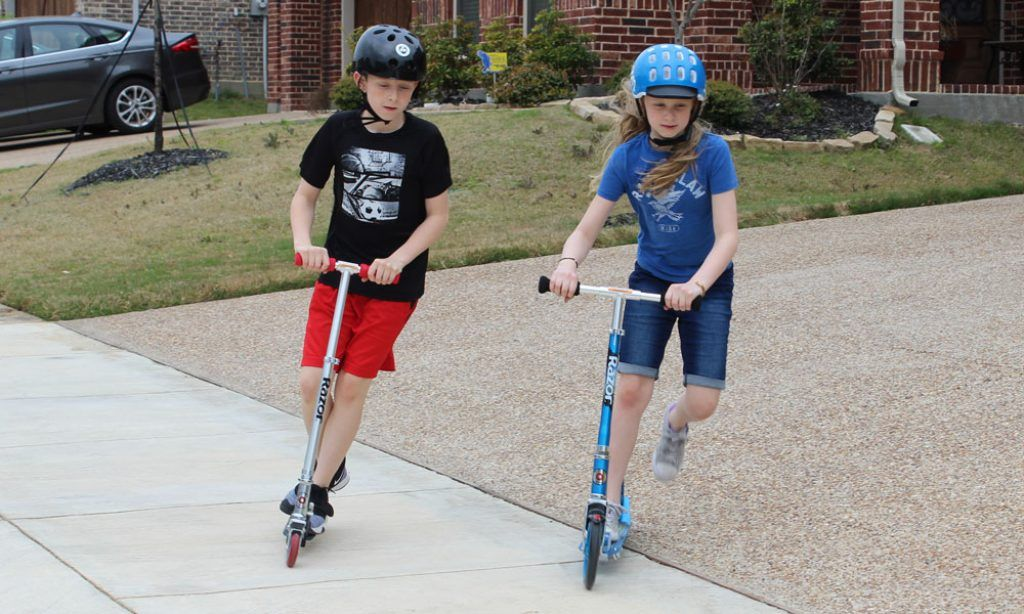 boy and girl riding the Razor Lux Razor A2 Kick Scooters