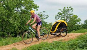 woman riding a bike with a burley bee bike trailer