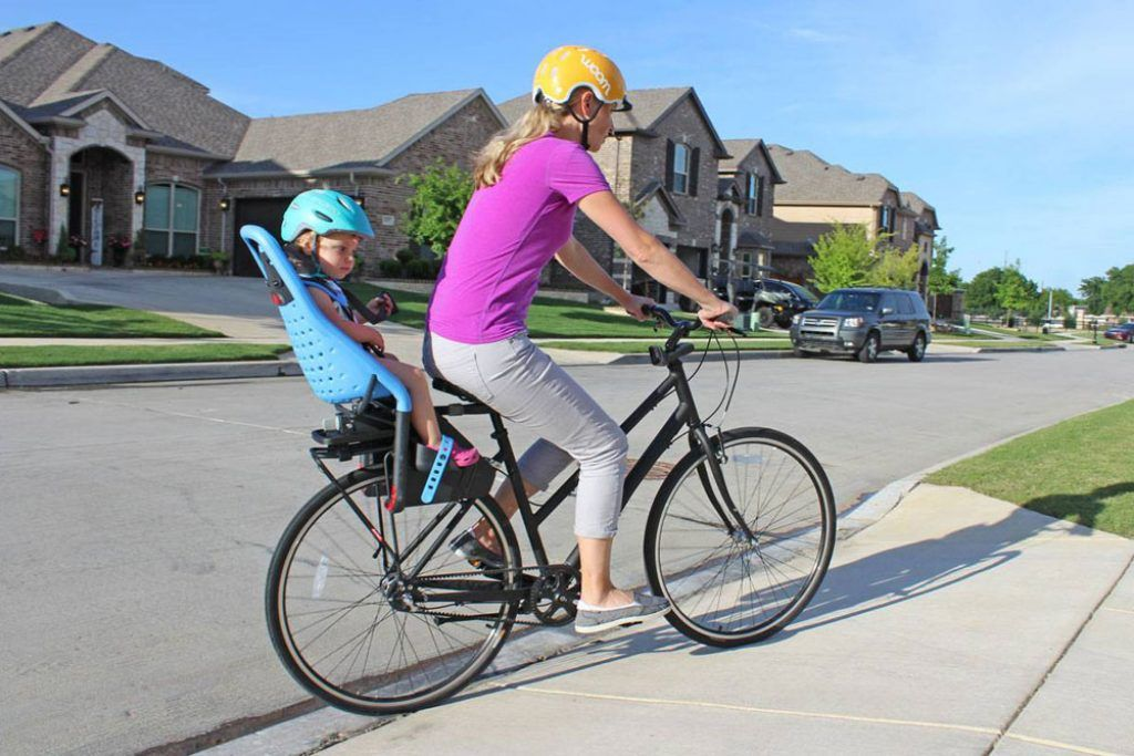 Mom riding with a child in the Thule Yepp Maxi child bike seat