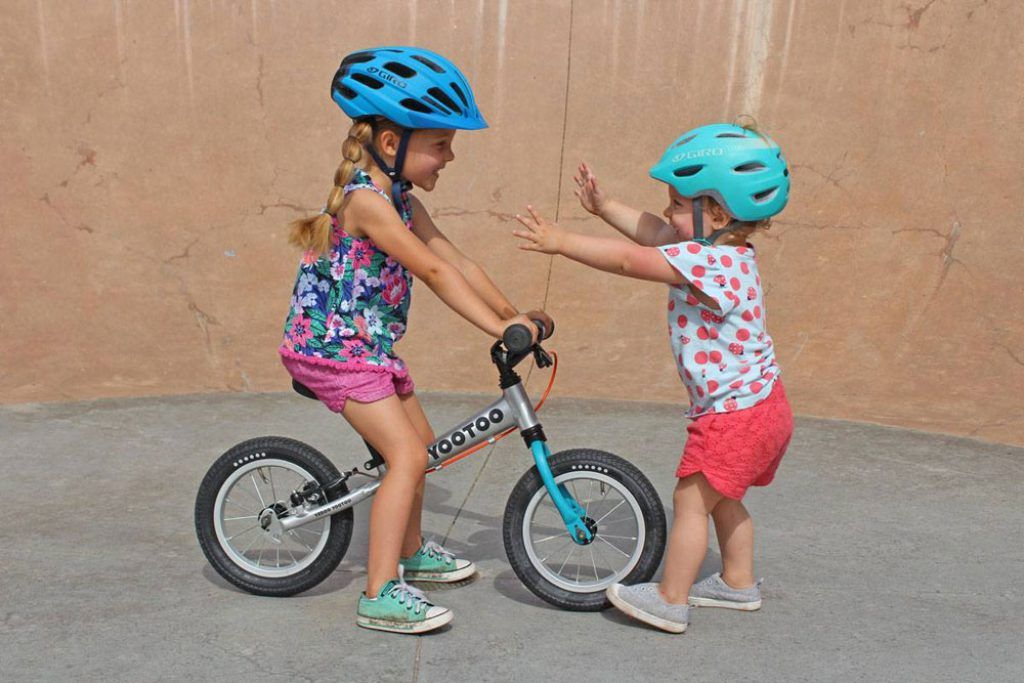 young toddlers playing while on rides a yedoo tootoo balance bike