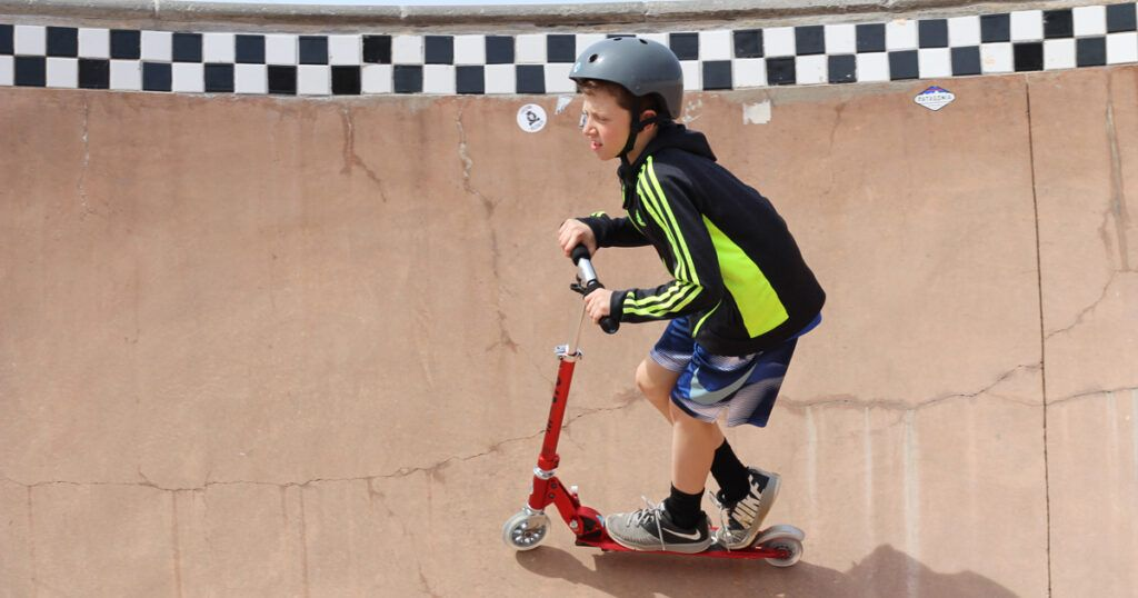 boy riding a scooter in a skate park