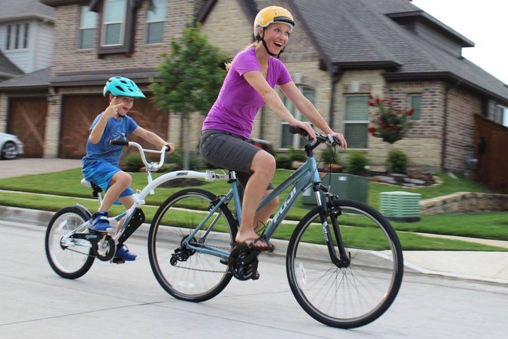 woman pulling a boy on a weeride co-pilot tag along bike