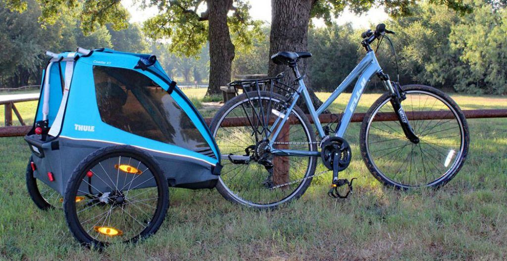 blue thule xt coaster bike trailer attached to a bike