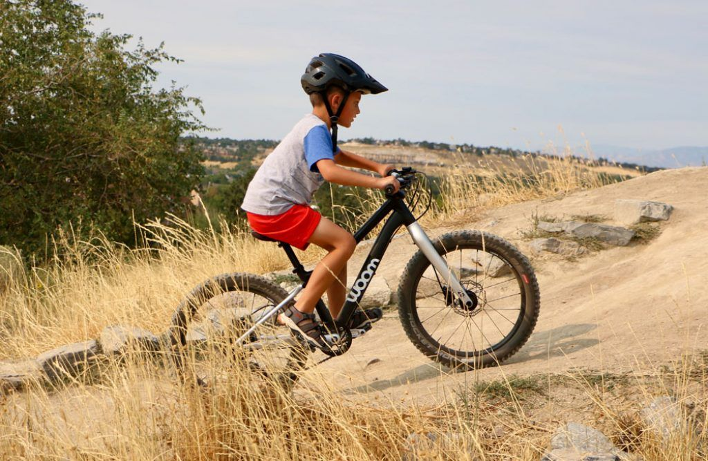boy riding the woom OFF 20-inch bike at a bike park