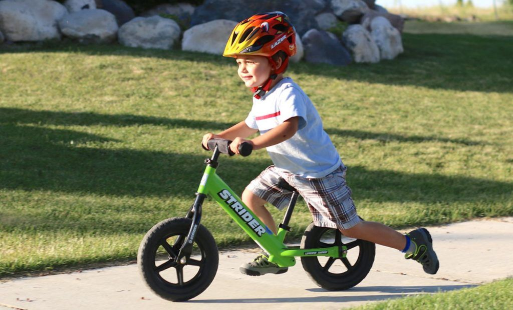 toddler riding a green Strider balance bike