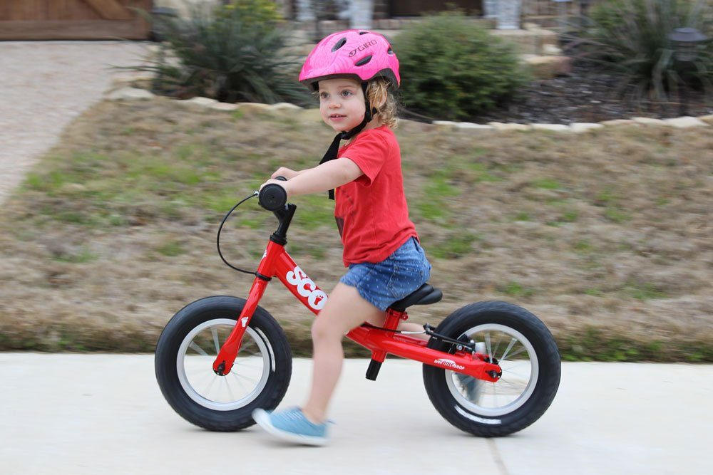 girl riding a red scoot balance bike