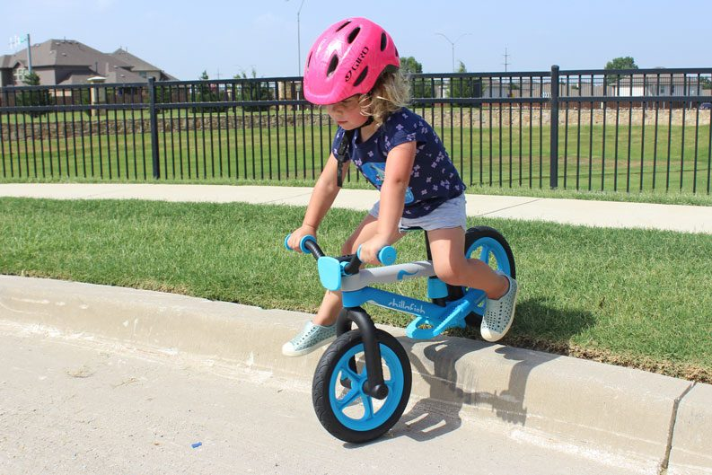 2 year old riding Chillafish BMXie2 balance bike over the curb