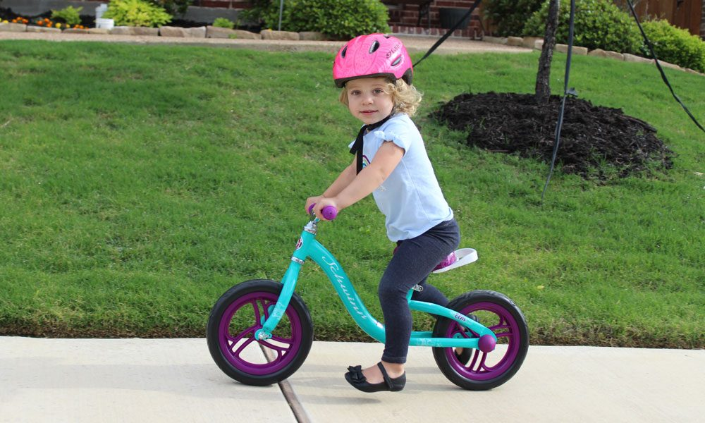 toddler riding a green schwinn balance bike