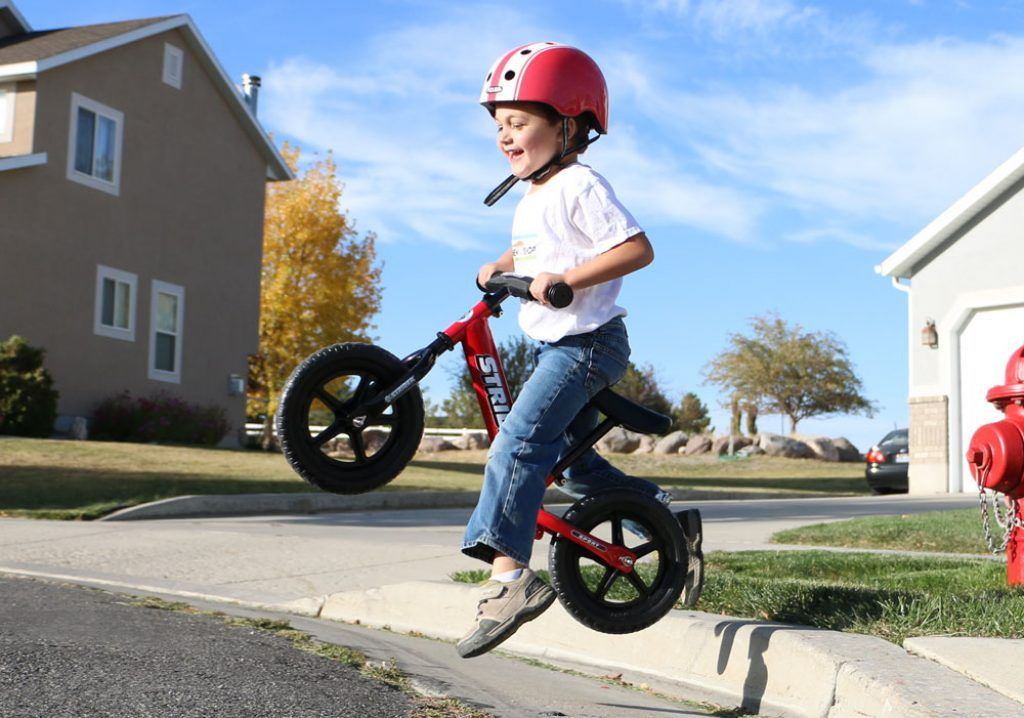 Young boy going off a jump on his red Strider balance bike