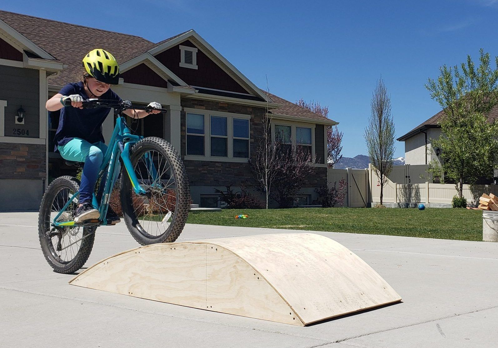 10 year old girl riding over a roller ramp on a mountain bike