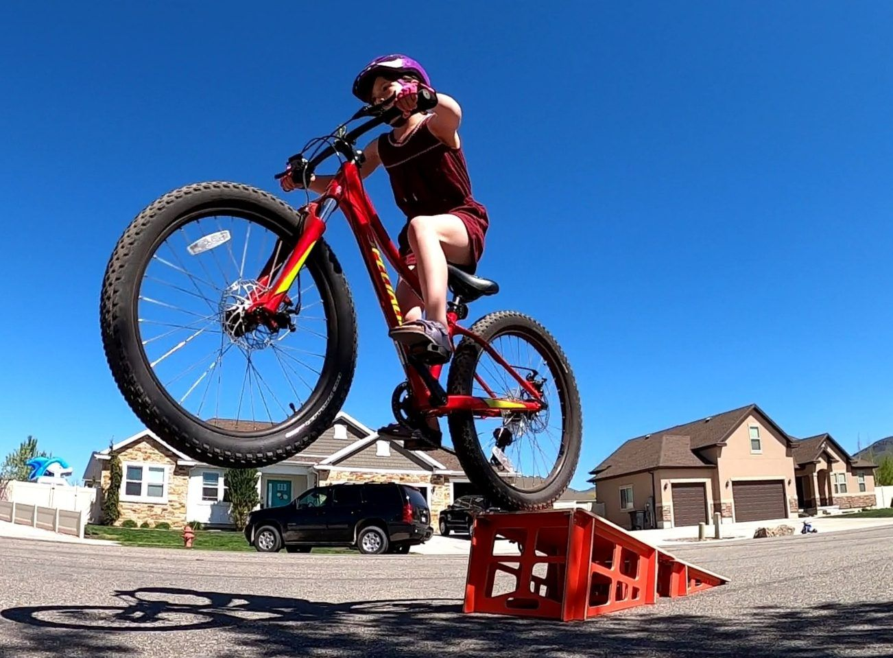 8 year old girl riding a mountain bike off a Byclex kicker ramp. The Yumpy is one of our favorite kids bike ramps.