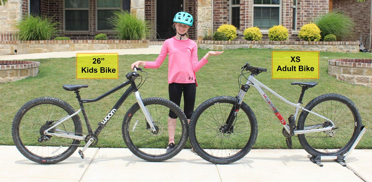 11 year old girl standing between a 26 inch kids bike and an XS adult bike
