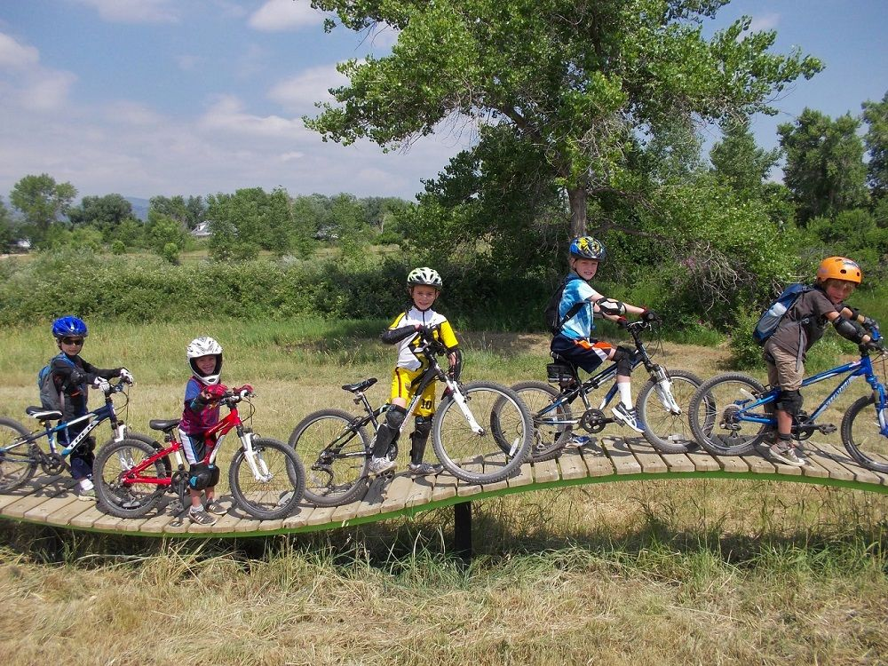 Valmont bike park in Boulder, CO with kids riding wood plank trail