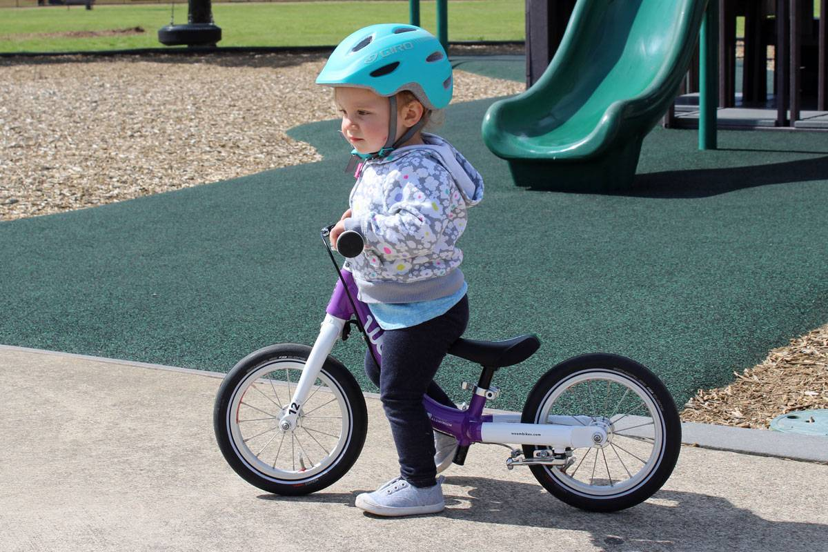 toddler riding the woom 1 balance bike at the playground