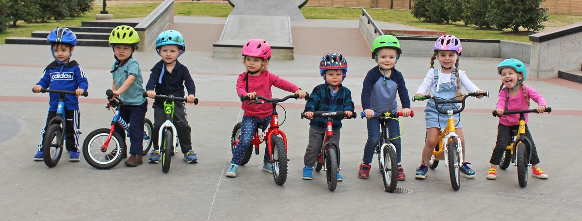 Balance bikes - a group of 9 toddlers lined up in a row, all on balance bikes at the skatepark