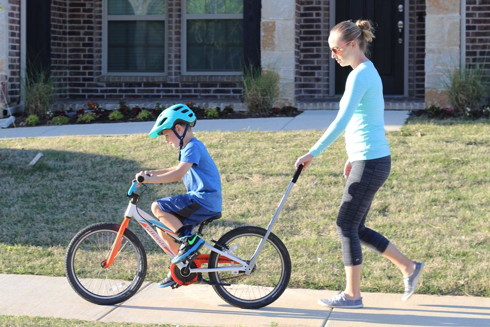 Mom holding the Balance Buddy to help her son learn to pedal his bike