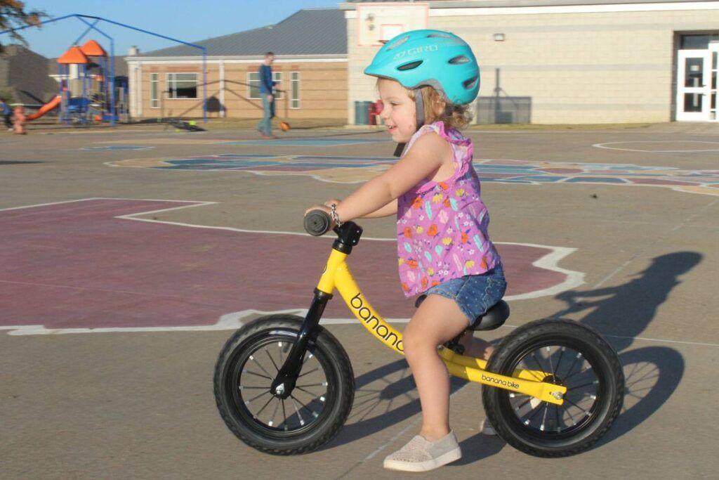 2 year old riding Banana Bike GT balance bike on playground