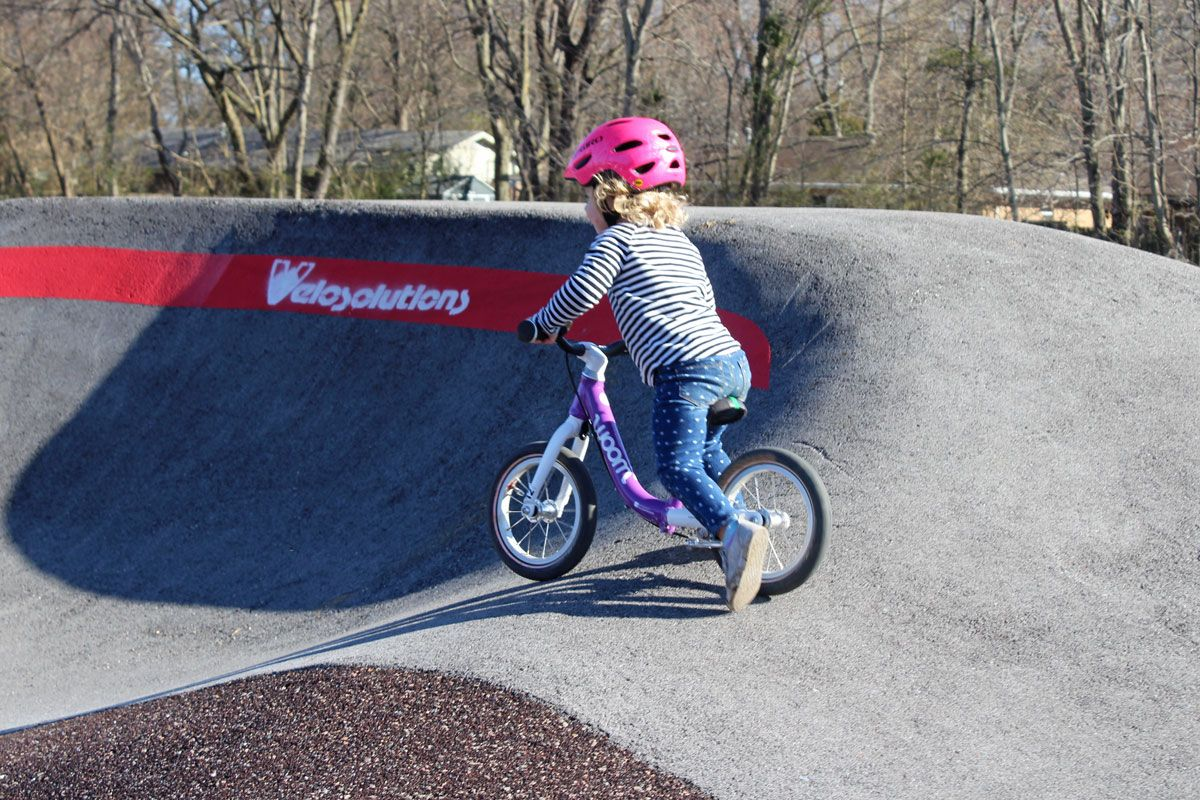 Toddler riding woom 1 balance bike on Velosolutions pump track at the Thaden School.