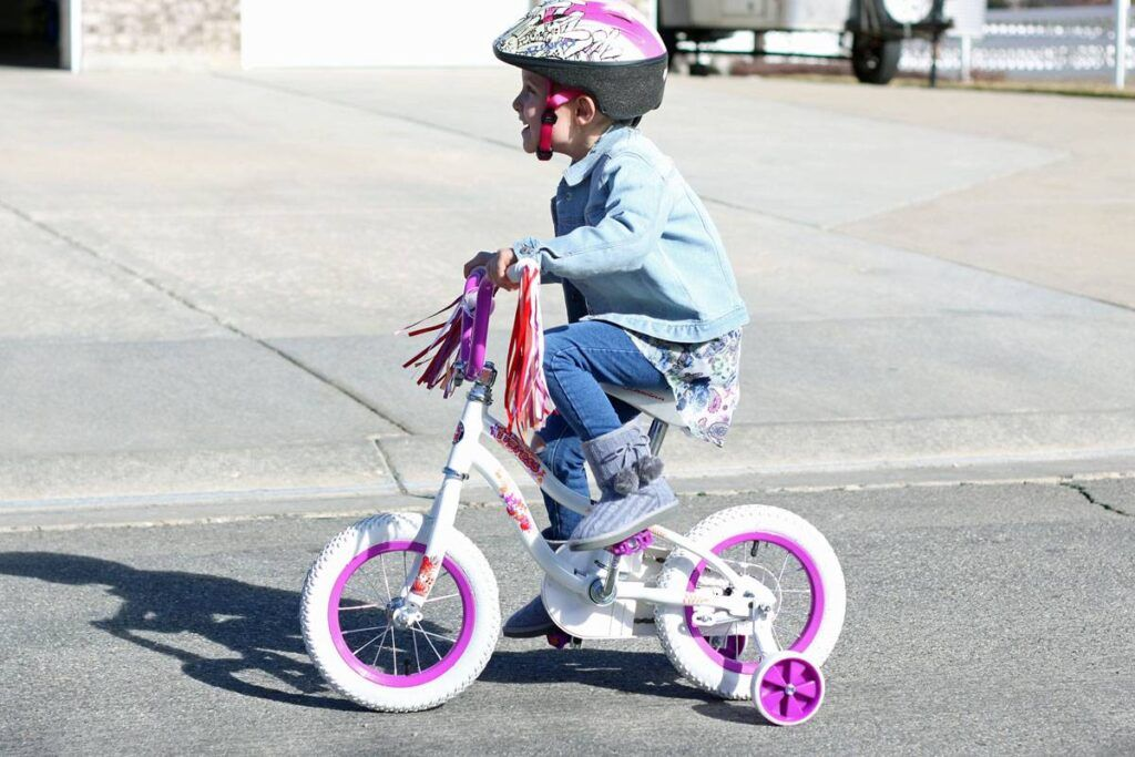 4 year old girl riding Schwinn girl's bike in white and pink