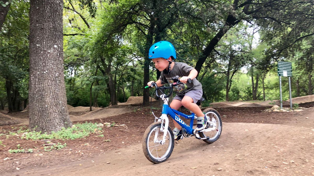 young shredder riding a blue woom bike at the 9th Street BMX bike park in Austin