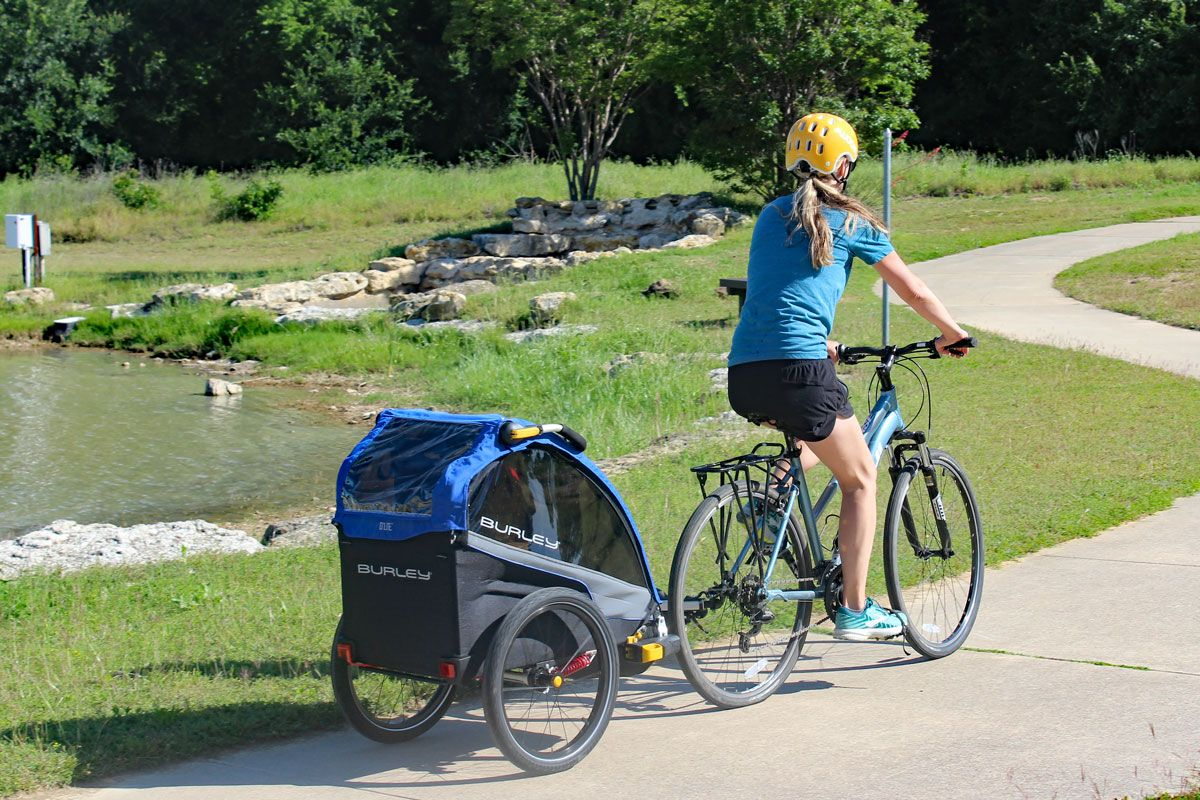 Mom riding down paved path pulling Burley D'Lite bike trailer