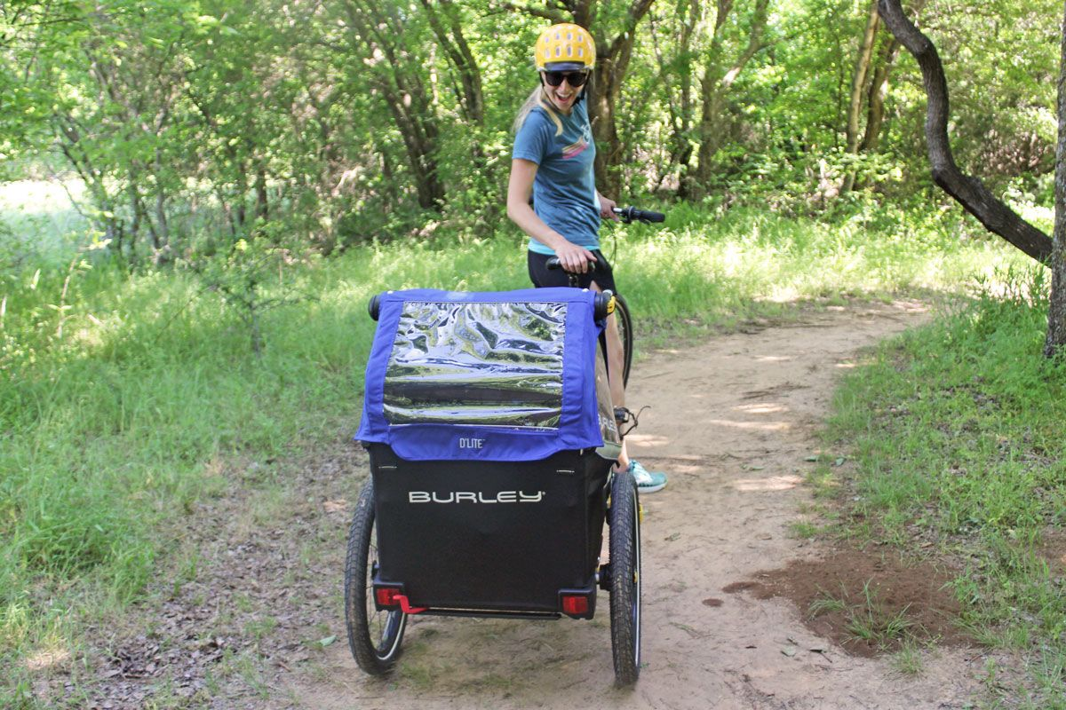 Mom turing around to look at her toddler in the Burley D'Lite single bike trailer