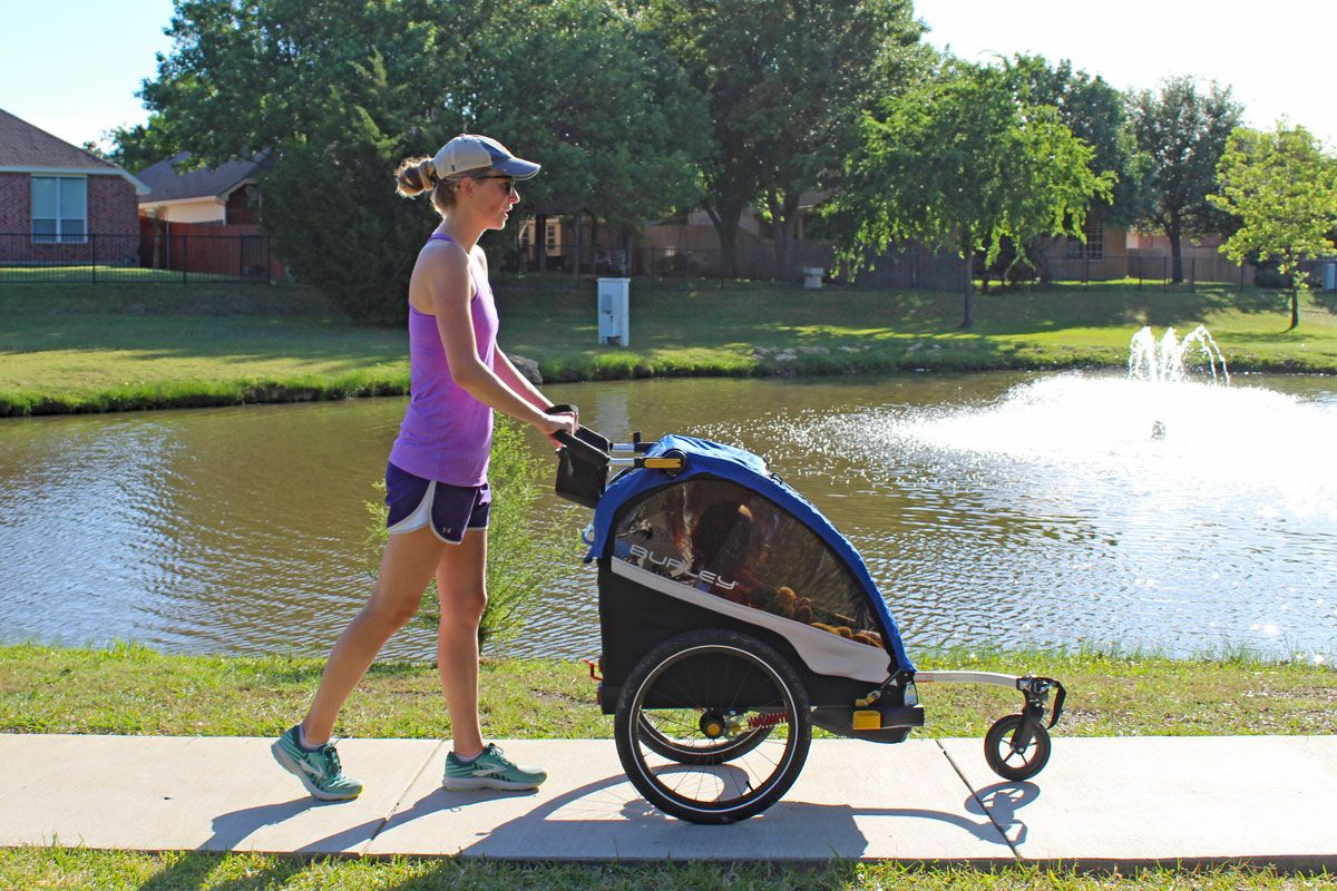 Mom pushing Burley D'Lite stroller by lake