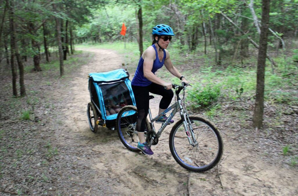 Mom powering up a dirt trail pulling the Burley D'Lite X double bike trailer