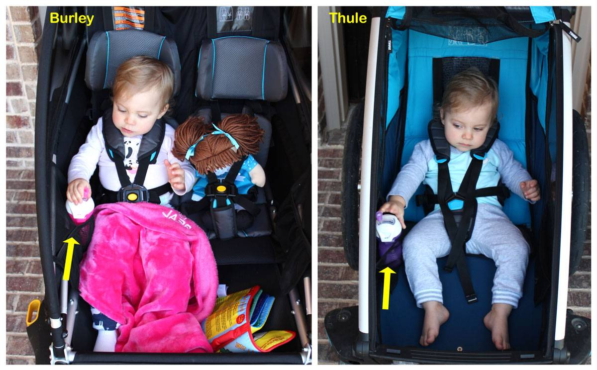 Burley D'Lite X vs Thule cross placement of mesh sippy cup holders. In the Thule, the toddler has to reach farther to grab the cup.