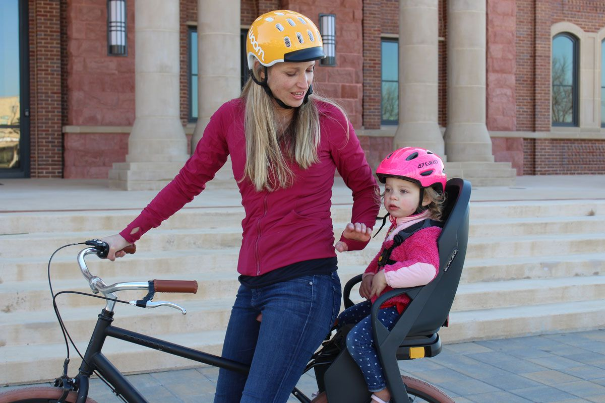 Mom smiling on bike with 2 year old toddler sitting in the Burley Dash child bike seat.