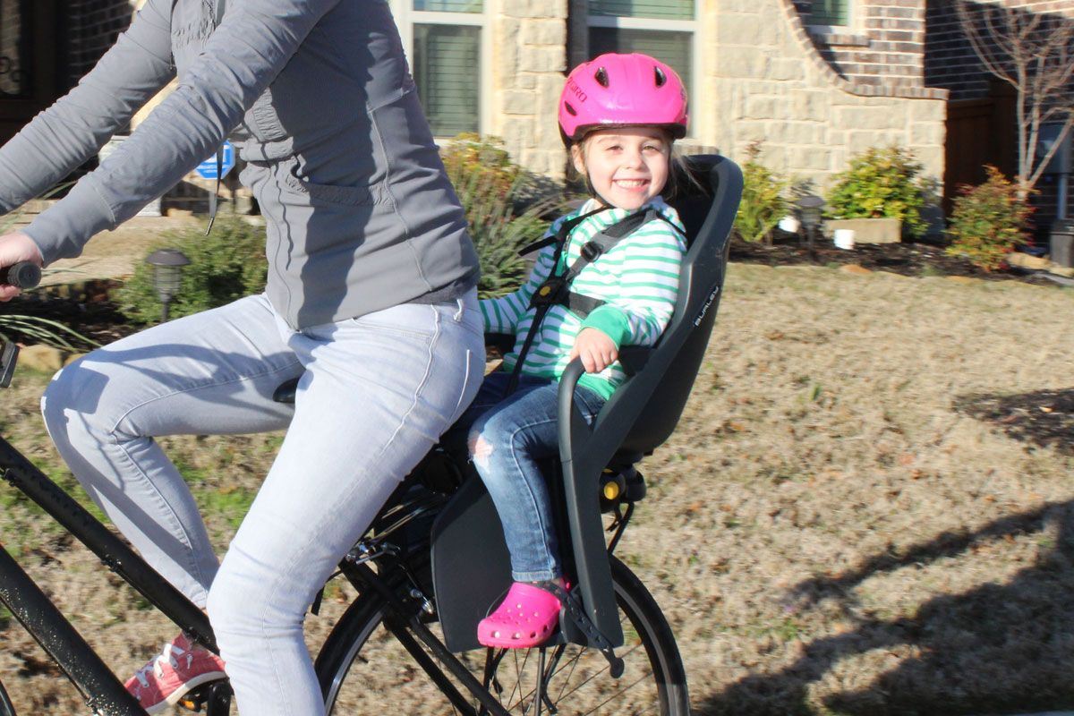 3 year old smiling large while riding in Burley Dash child bike seat