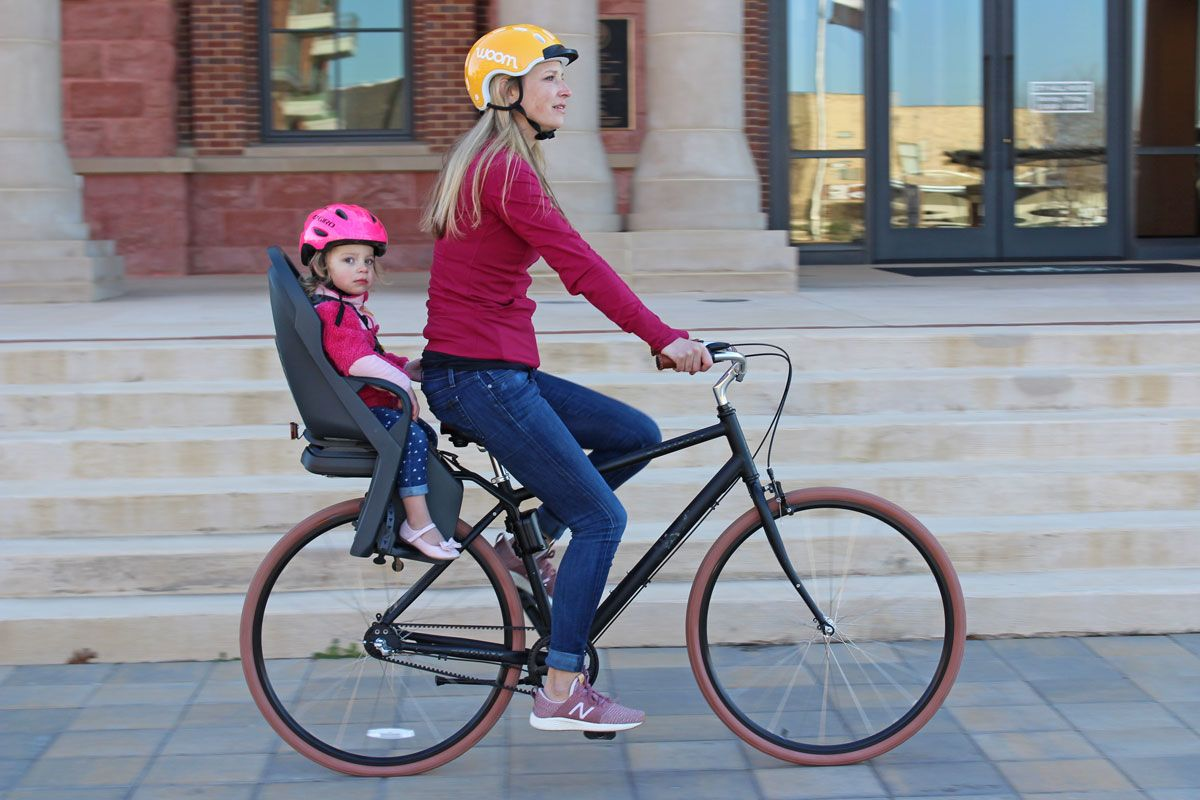 Mom riding Priority Bike with 2 year old toddler sitting in the Burley Dash child bike seat.