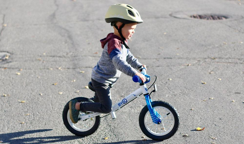 4-year-old gliding ByK E-200L balance bike in the street