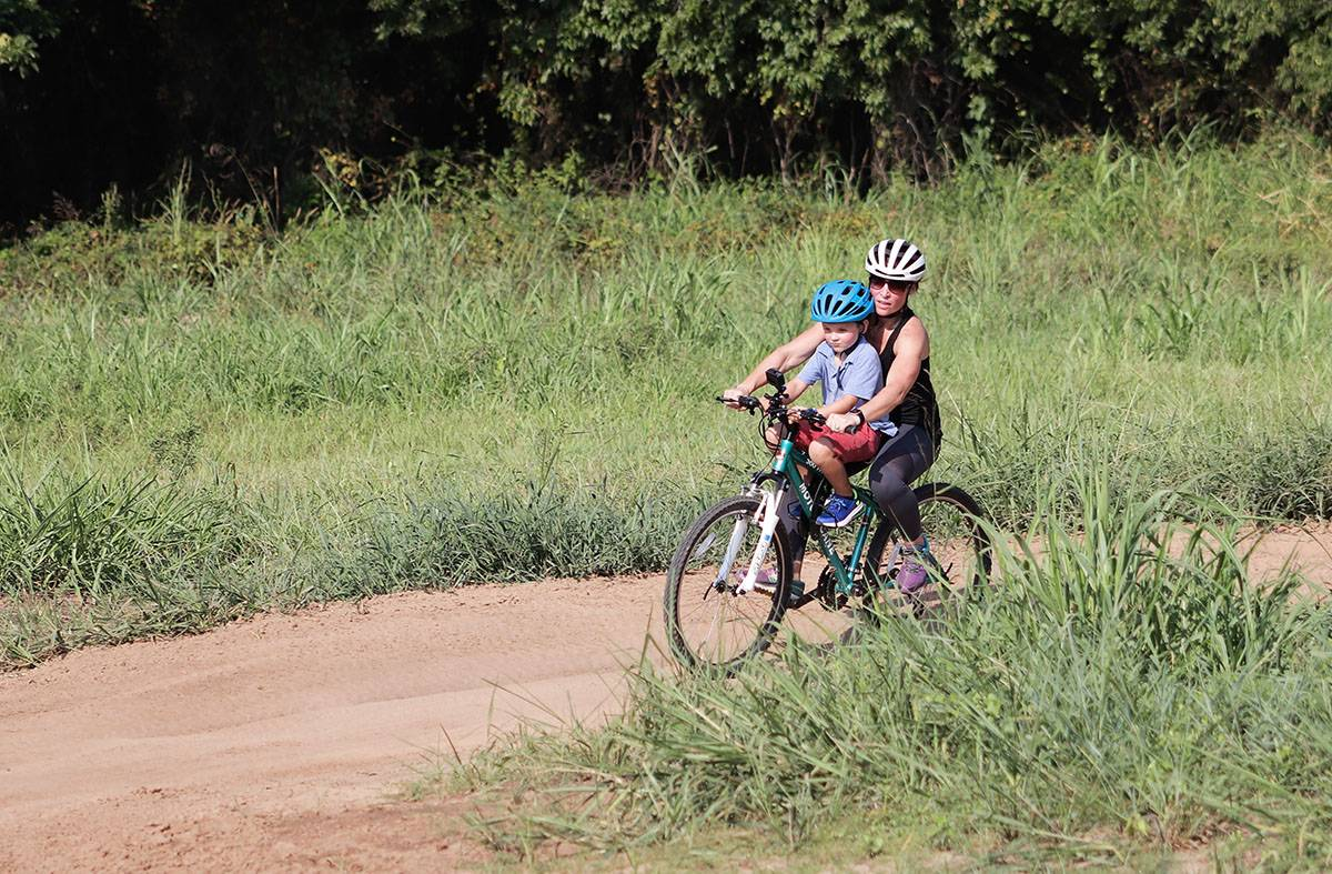 6 year old boy riding Do Little child bike seat on sand track with woman.