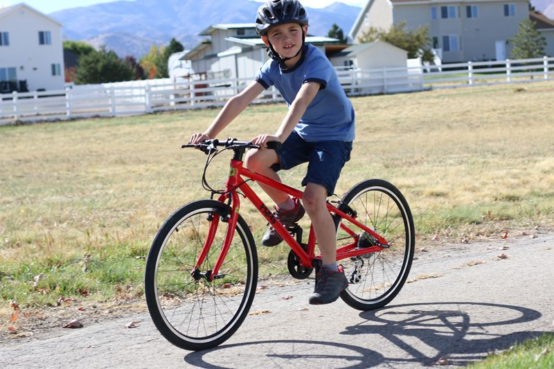 9 year old riding a red frog 62 24 inch kids bike