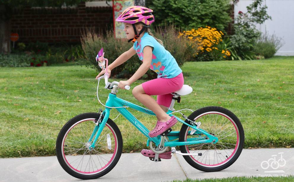 a 7 year old riding a teal and pink 20 inch bike by Guardian