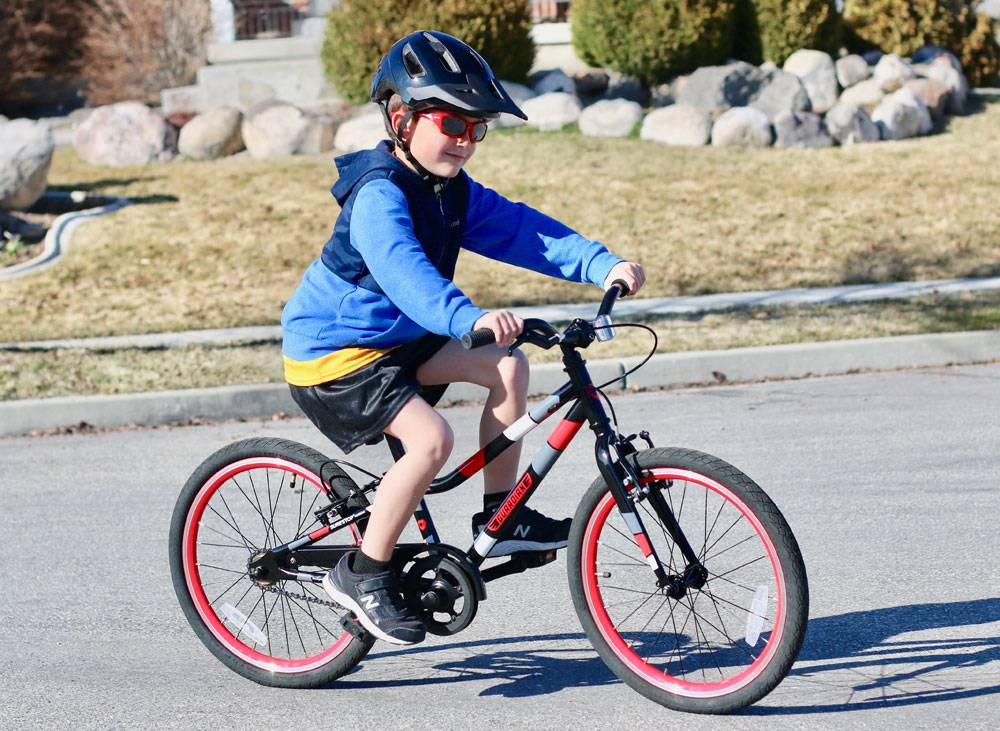 "7-year-old riding Guardian Ethos 20"" Small bike in black and red"