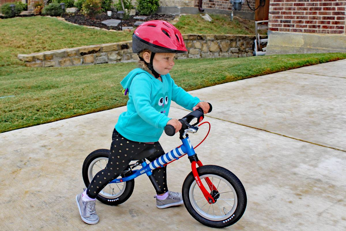 2 year old riding balance bike while wearing Joovy Noodle helmet