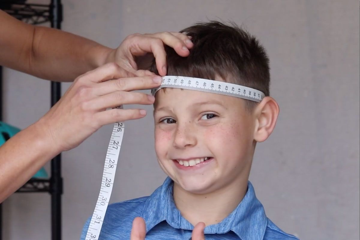 Mom measuring her son's head with a soft tape measure to determine the right kids bike helmet size