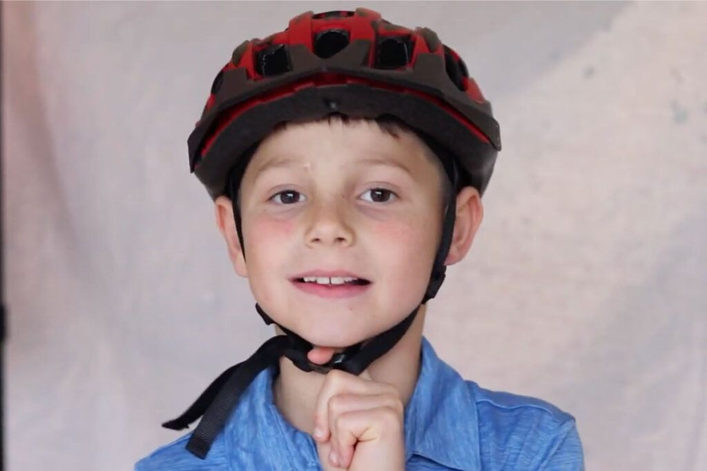 kid putting his finger beneath the strap of his helmet to make sure its the right size